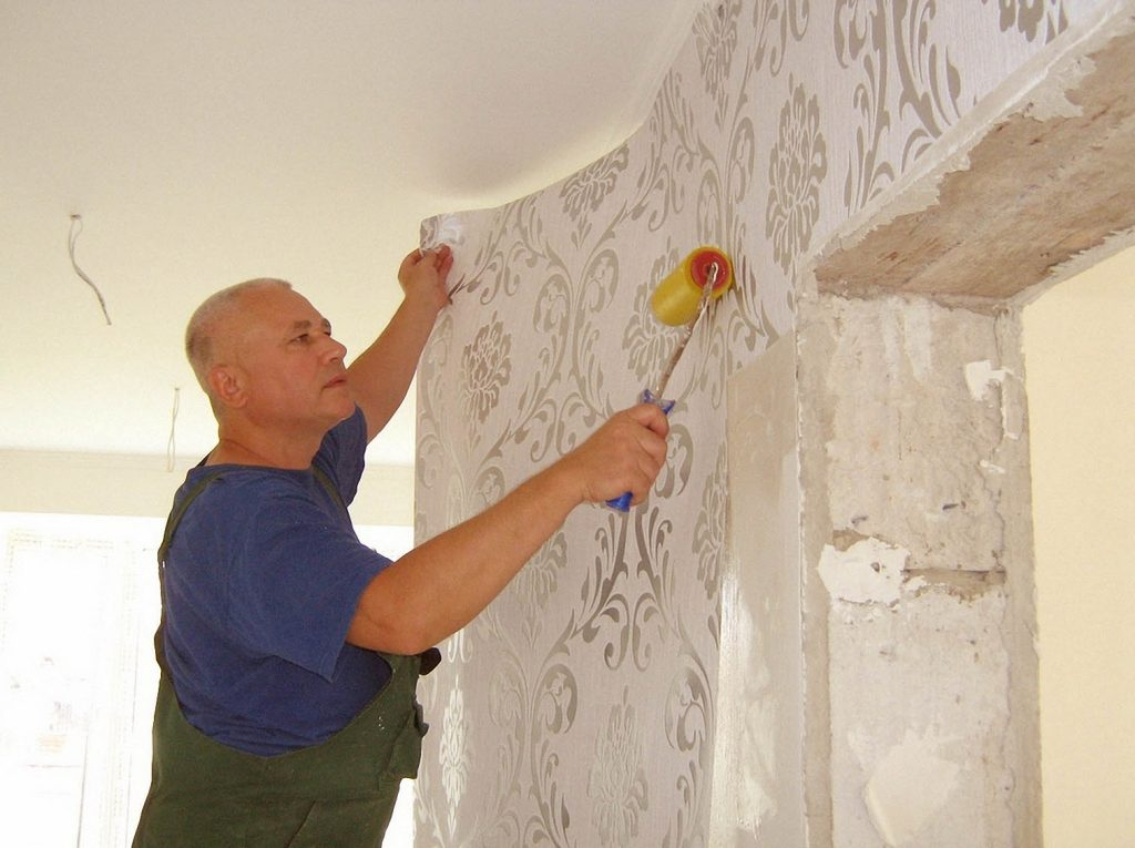 A man sticking wallpaper on the wall