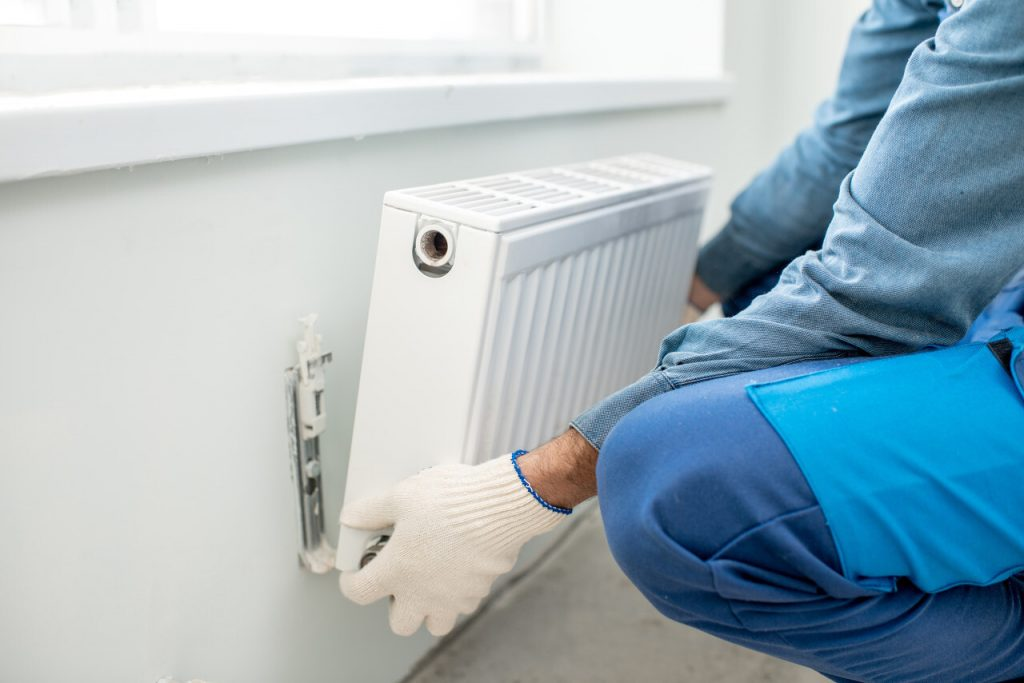 A man installing a radiator