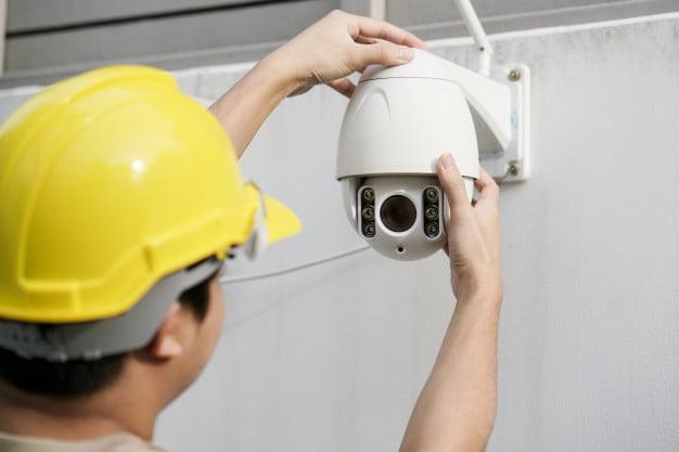 close-up-male-technician-fixing-cctv-camera-wall