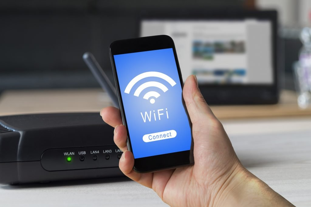 a mobile phone on a hand , a router , wifi connection