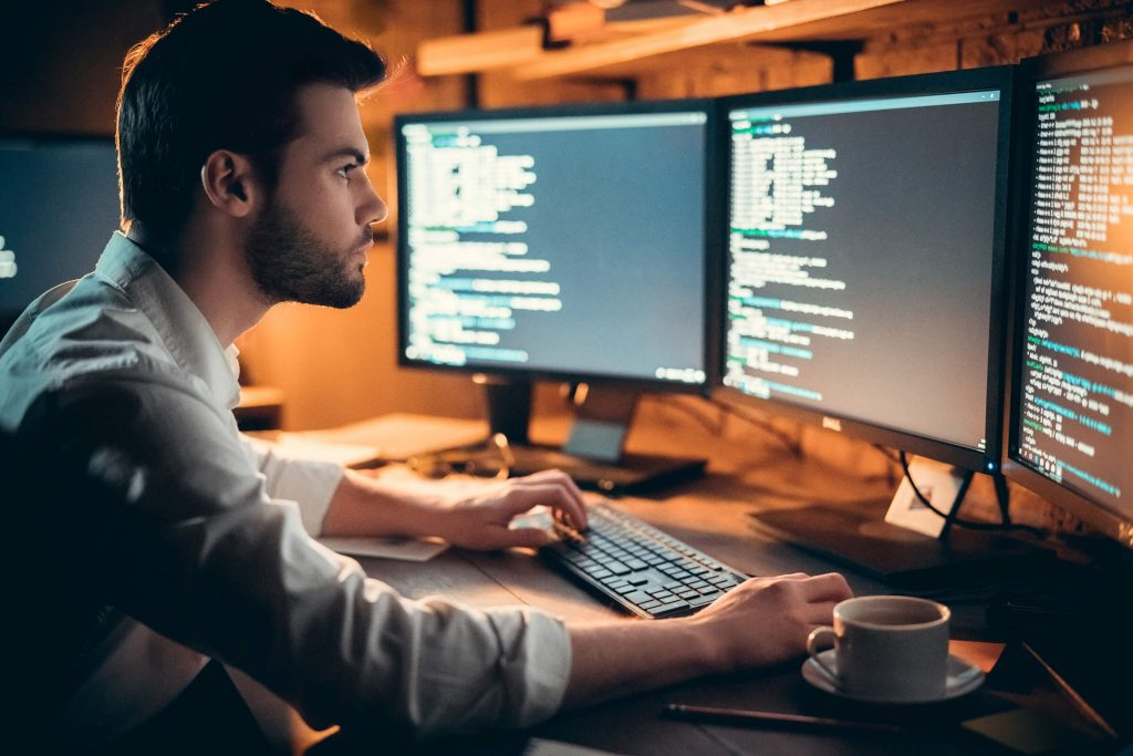 a man who is coding with 3 computer